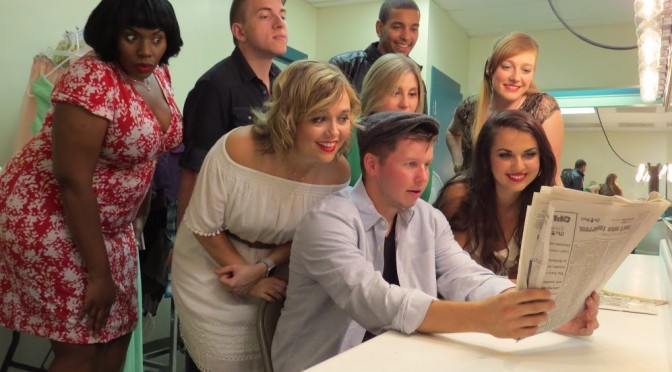 The cast eagerly read the review of their new show.  Photo credit: Rebecca Seezen